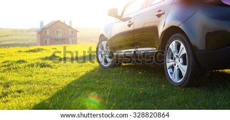black car without a trade brand on grass at sunset - stock photo