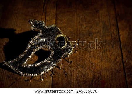Black carnival mask with golden decoration on rustic wooden table - stock photo