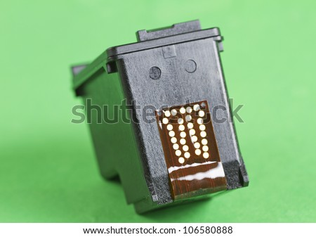 Black cartridge for a printer over a green background - stock photo