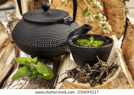 Black cast iron teapot and cup of tea with mint on old wooden table.