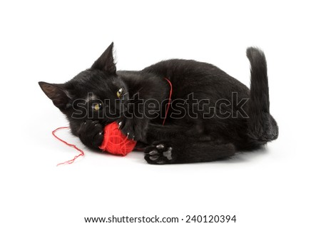 black cat gnaws a red ball - stock photo