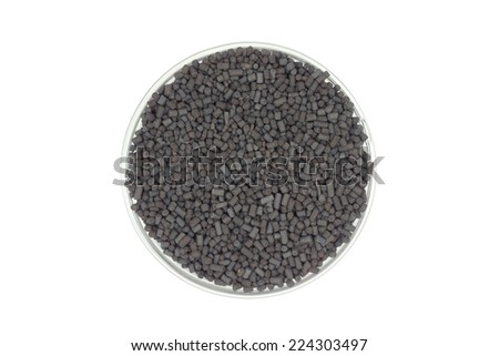 black catalyst pellets in a glass container on a white background