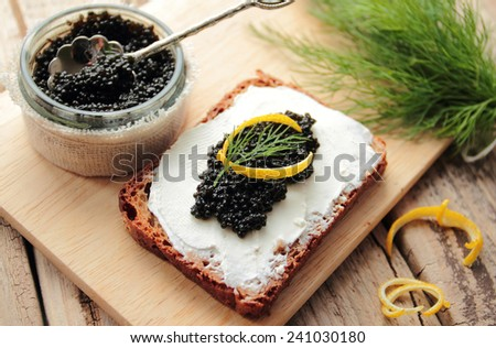 Black caviar and cream cheese on a dark bread - stock photo