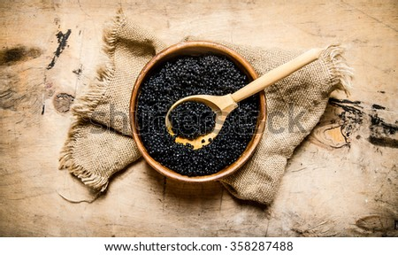 Black caviar in a wooden bowl on old fabric. On a wooden table. Top view - stock photo