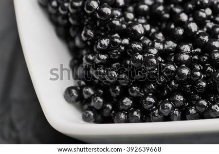 black caviar in the white ceramic bowl close-up on the dark background horizontal - stock photo