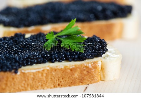 Black caviar on a slice of bread with parsley - stock photo