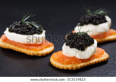 Black caviar served on crackers with salmon and cream cheese.