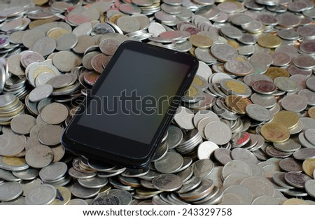 Black cell phone on pile of coins - stock photo