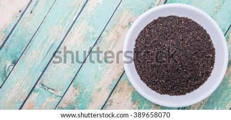 Black Ceylon tea in white bowl over wooden background