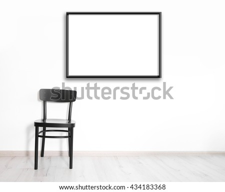 Black chair and empty picture frame on wall background