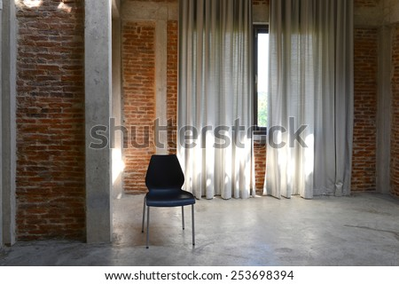 Black chair and sunlight from window on the brick walls in the room - stock photo