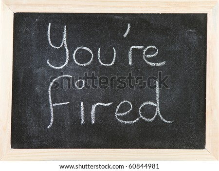 Black chalk board with wooden framed surround with the words You're Fired.