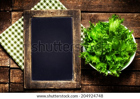 Black chalkboard for menu and fresh salad over wooden background. Diet Food Restaurant and healthy lifestyle concept.  - stock photo
