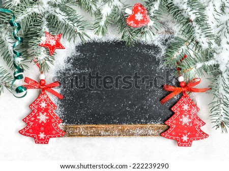 Black chalkboard on snow decorated with Christmas tree branches, wooden toys, space for your text - stock photo