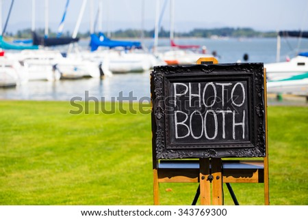 Black chalkboard sign with white chalk at a wedding reception marking the spot for the photobooth. - stock photo