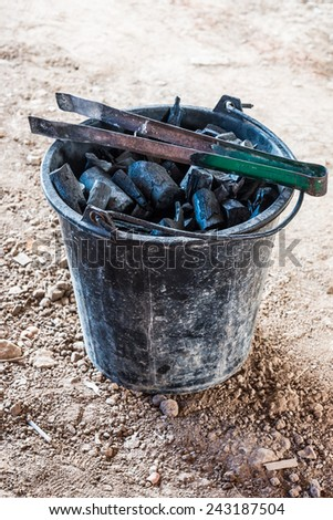 Black charcoal in the bucket of rural restaurant. - stock photo