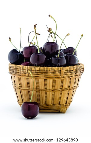 Black cherries sitting in a basket isolated on a white background. - stock photo