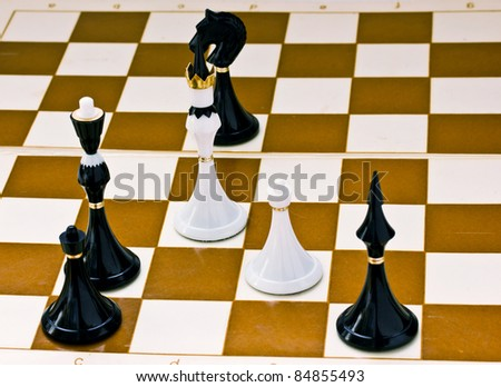 Black chess beats white king and pawn on board - stock photo