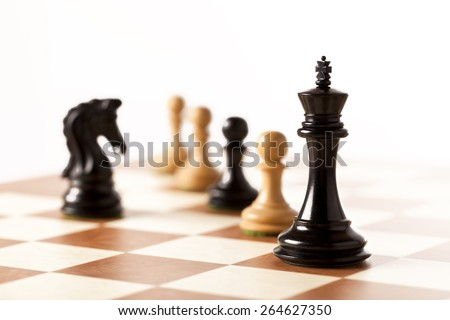 Black chess king and knight on a chessboard with pawns in the background - stock photo