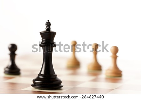 Black chess king on a chessboard  with white pawns in the background - stock photo