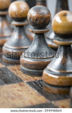 black chess pawns row with focus on central piece