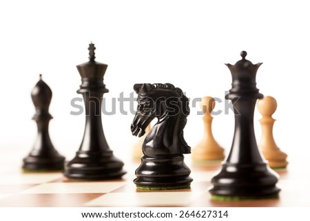 Black chess pieces with white pawns in the background on a chessboard - stock photo