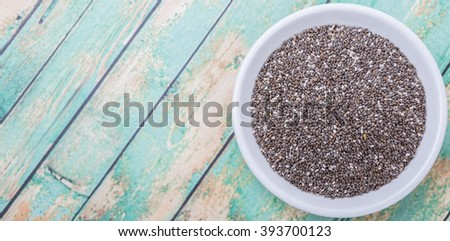 Black chia seed in white bowl over wooden background