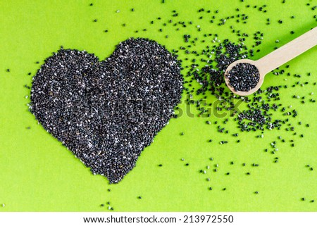 Black chia seeds arranged in heart shape with small spoon on green background - stock photo