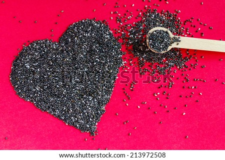 Black chia seeds arranged in heart shape with small spoon on red background - stock photo