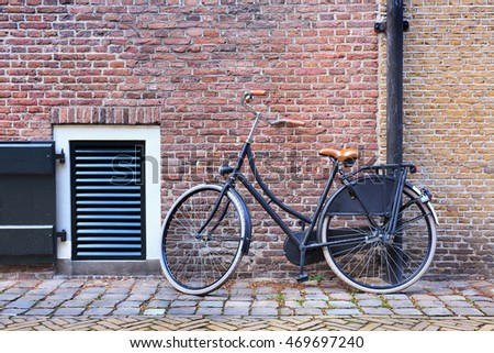 Black classic bicycle parked against a red brick wall, Amsterdam, Netherlands