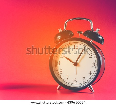 Black classic style alarm clock on red background with vintage tone colour, Clock concept, Retro clock at Ten o'Clock and Five minute.