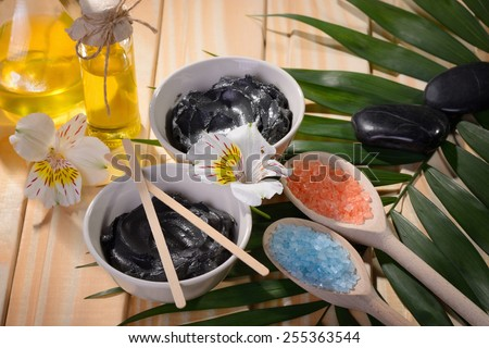 black clay from the Dead sea  two bowls for procedures stones for massage bottle with butter buds of flowers on the table color birch and fern and wooden sticks two wooden spoons salt blue and orange - stock photo