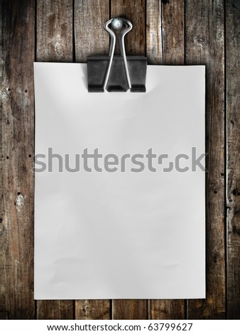 Black clip and White blank note paper hang on wood panel - stock photo