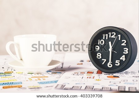 Black clock and white coffee cup on desktop with business charts