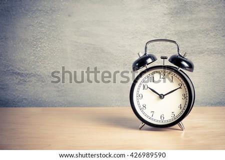 black clock on wood table - stock photo