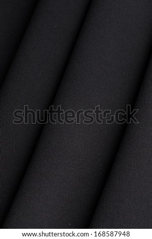 Black cloth with straight folds texture closeup - stock photo