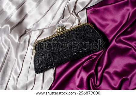 Black clutch on a silk background - stock photo