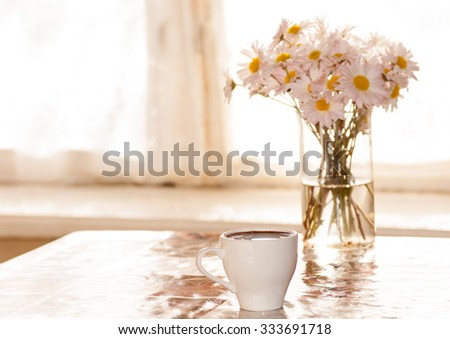 black coffee and chamomile in a vase on the table in front of the window in the morning - stock photo
