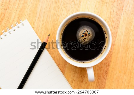 Black coffee and notepad on wooden table