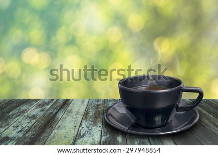 Black coffee cup on vintage wooden with shiny sunlight bokeh background. - stock photo