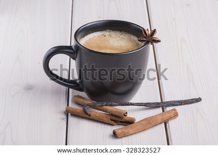 Black coffee cup with anise star, cinnamon and vanilia