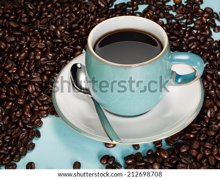 Black Coffee in a blue cup amongst fresh unground beans - stock photo
