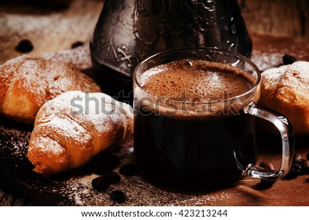 Black coffee in a glass cup, steel coffee maker, sprinkled with powdered sugar croissants, dark vintage wooden background with strong shadows, selective focus