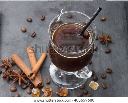 Black coffee in a glass on a black board with cinnamon sticks, spices, coffee beans, anise stars, sugar and caramel. Hot drink - frappe, latte, cappuccino. Top view a cup of coffee.  - stock photo