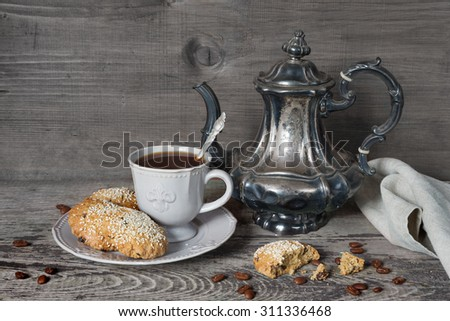 Black coffee in a Victorian cup and oatmeal cookies sprinkled with sesame seeds on a porcelain plate as well as old silver coffee pot and gray linen napkin on a background of old unpainted boards - stock photo