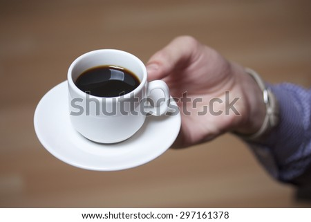 black coffee in a white cup and saucer, coffee in hand