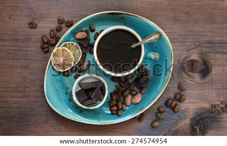 Black coffee in blue vintage cup and chocolate on a old dark wooden boards - stock photo