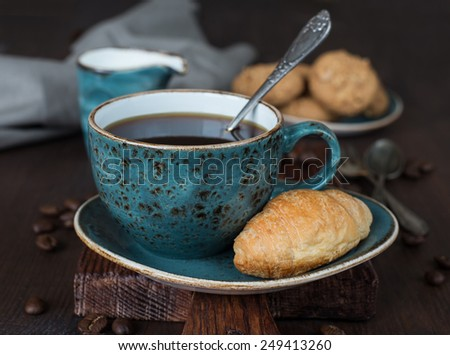 Black coffee in blue vintage cup on old dark cutting board - stock photo