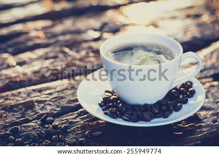 Black coffee in the cup on old wood table with coffee beans - vintage color style with soft focus - stock photo