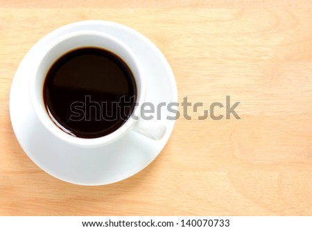 Black coffee in white cup on a wooden table